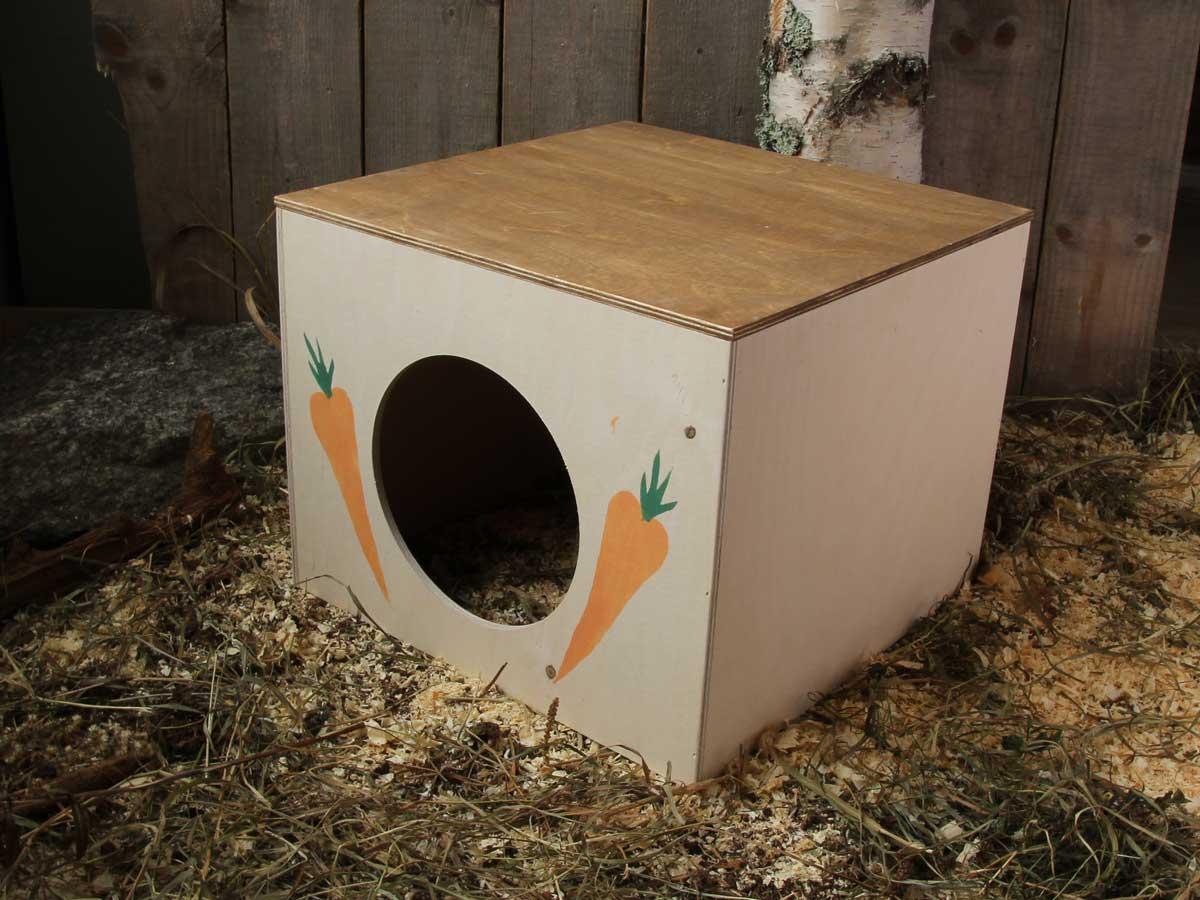 Keskikokoisen kanin kuutiomökki, porkkanan kuvat oven molemmin puolin, muuten valkoinen.